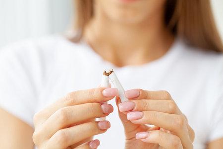 Stop smoking, woman holding a broken cigarette Stock fotó