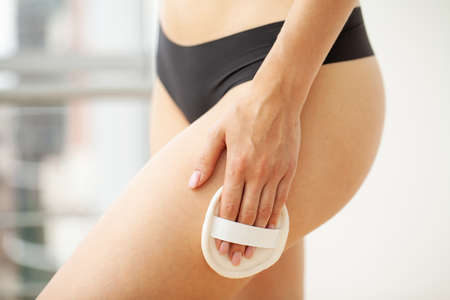 Cellulite treatment, woman arm holding dry brush to top of her leg.