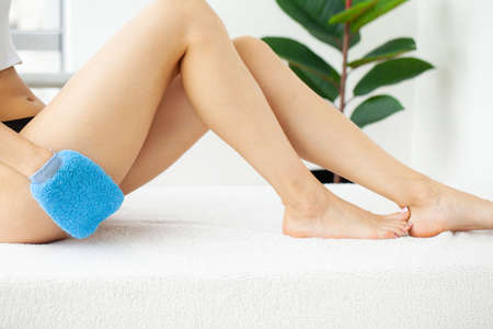 Cellulite treatment, woman arm holding blue dry brush to of her leg.