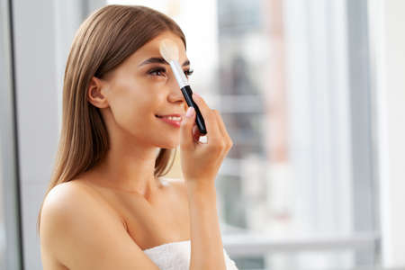 Pretty woman doing makeup at home in front of mirror
