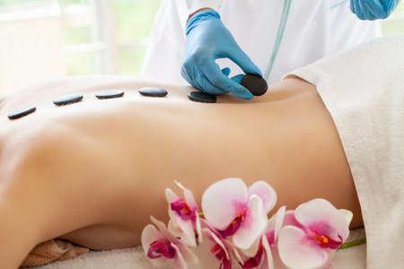 Young woman getting hot stone massage in spa salon. 版權商用圖片
