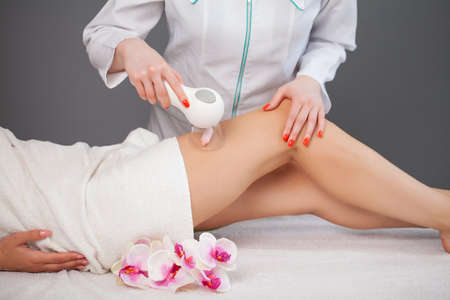 Woman getting anti-cellulite massage of leg with use of vacuum cans Stock fotó