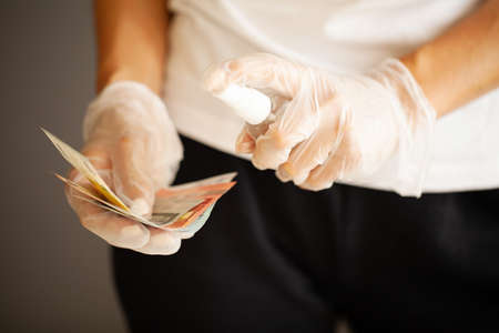 Close up woman disinfect money with antiseptic. Stock fotó