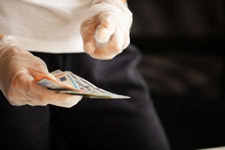 Close up woman disinfect money with antiseptic. 版權商用圖片