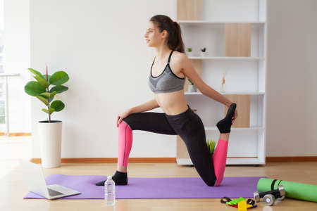 Attractive young woman doing yoga stretching yoga online at home.