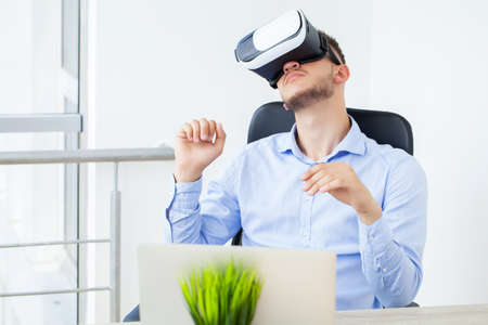 Young man wearing virtual reality goggles in modern coworking studio.