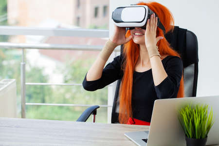 Young woman wearing virtual reality goggles in modern coworking studio.