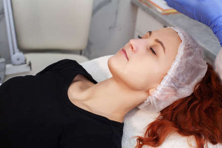 Patient applying electrical stimulation therapy on face.