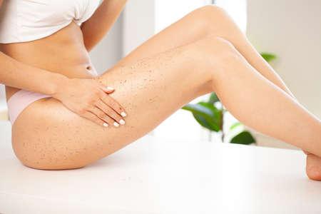 Closeup woman legs with coffee anti-cellulite wrapping scrub.