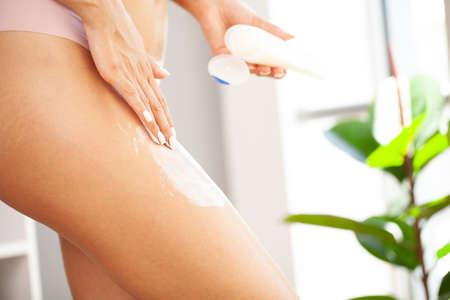 Female applying cosmetic cream from cellulite on leg Standard-Bild