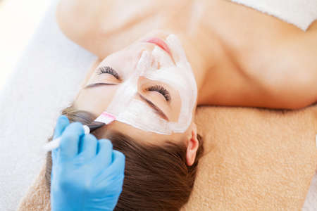 Attractive funny woman with a clay spa mask on her face. Standard-Bild