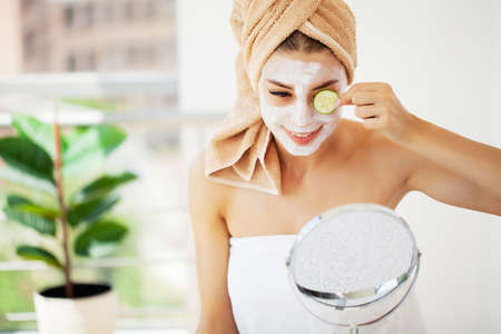 Woman applying mask on her face and looking in the mirror. Standard-Bild