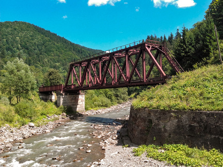 Red railroad bridge on mountain river Stock Photo