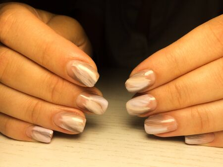 Nails care. Woman hands with  manicure on dark background. Closeup photo. Healthcare. Spa