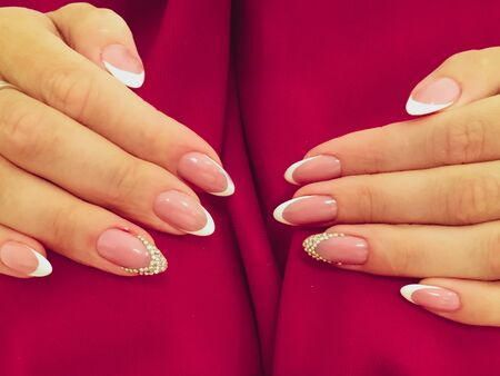 Woman hands with manicure on red background. Closeup photo. Delicate colors Reklamní fotografie