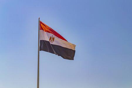 Flag of Egypt on flagpole against clear blue sky. Sharm-el-Sheikh, Egypt