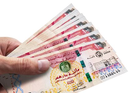 Hand holding dirhams of United Arab Emiratess. AED. Currency of UAE.
