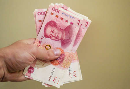 100 Chinese Renminbi banknotes in hand