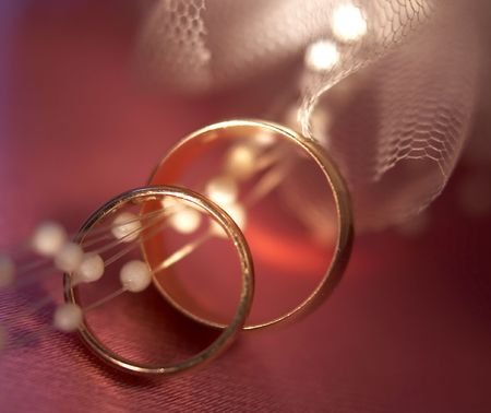 Wedding rings on a pink background with a veil photo
