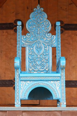 Imperial wooden throne of dark blue color with woodcarving costing on a porch of the house