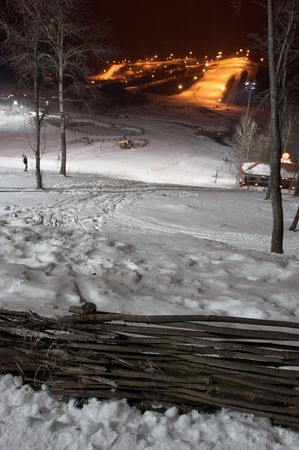 Mountain-skiing slope at night. In the foreground ïëåòåíûé a fence. Small houses-hotels are visible