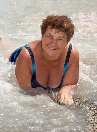 The happy elderly lady on a beach, in water.