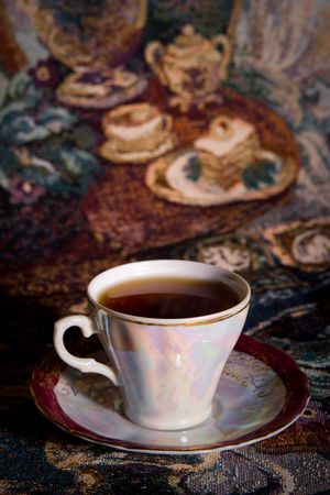 olden: Cup of tea of ancient service in style of olden time on a gobelin Stock Photo