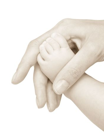 Foot of the child in a hand of mum. It is isolated on a white background.