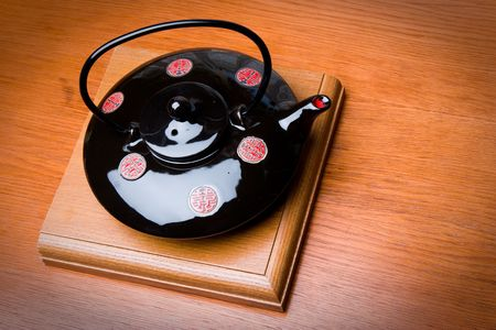Brewing teapot in the Japanese style on an eminence against wall-paper with drawing photo