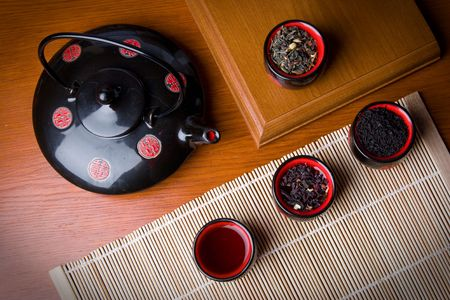 eminence: Brewing teapot in the Japanese style on an eminence against wall-paper with drawing Stock Photo