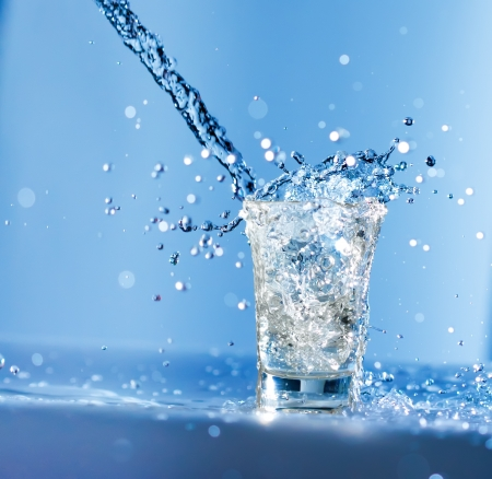 Water flowing in a glass with huge splashes