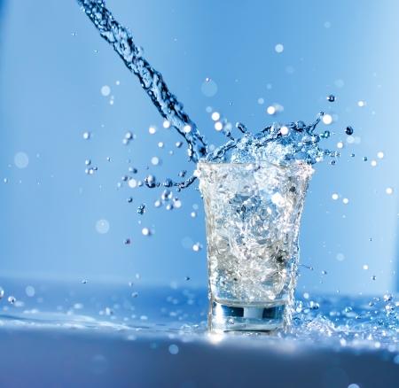 acqua vetro: Acqua che scorre in un bicchiere con enormi spruzzi  Archivio Fotografico