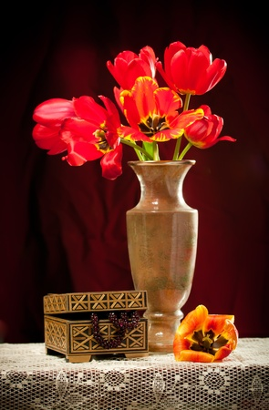 Still-life with a bouquet of tulips to a vase and a chest Stock Photo
