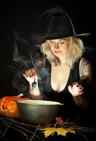 The charming witch cooks the potion on the eve of Halloween. photo