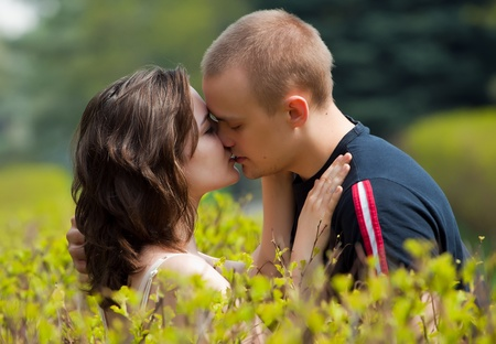 kissing loving couple in the spring in park photo