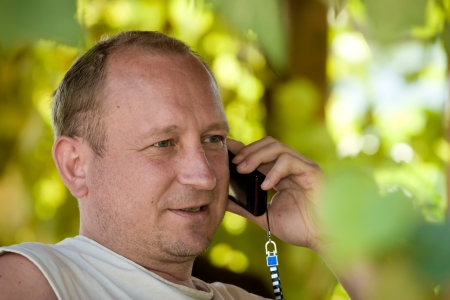 speaks: the man speaks by phone sitting in an arbor twined grapes