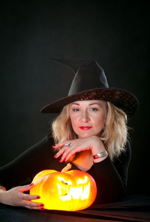 The charming witch cooks the potion on the eve of Halloween  photo