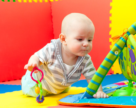 playmat: portrait of the nice child with brown eyes who plays on a developing rug