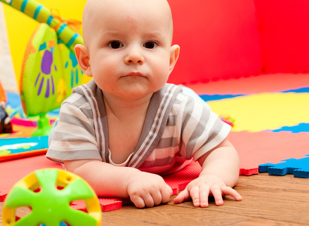 portrait of the nice child with brown eyes who plays on a developing rug photo