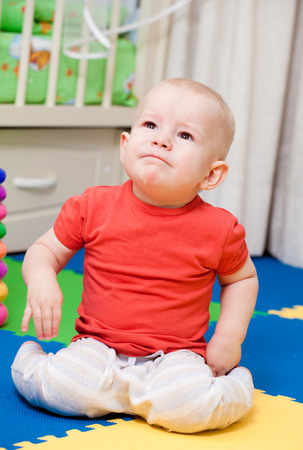 cries: baby plays in a nursery