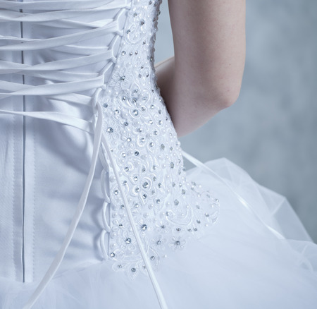 the bride puts on a white dress, a view from a back Stock Photo
