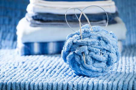 knitted clothes for newborn, stacked, lying on the table
