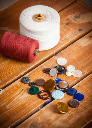 bobbins with thread and needles, striped fabric. Old sewing tools on the old wooden background. 写真素材