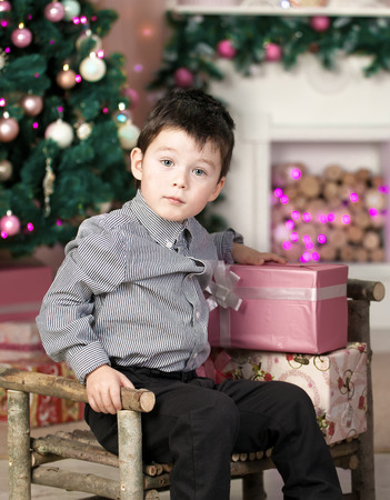 boy sitting on a chair in the room, painted for Christmas