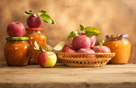Jam made from apples in glass jars, apples in a wicker basket