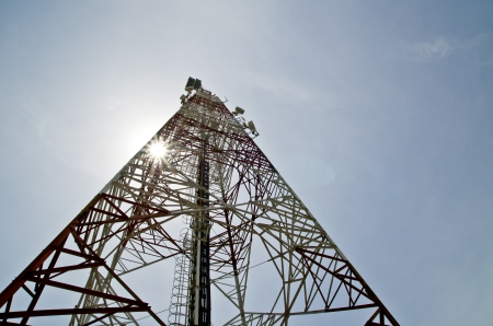 communications tower with antennas against blue sky photo
