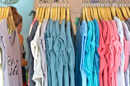 a colorful row t-shirts hanging on hangers photo