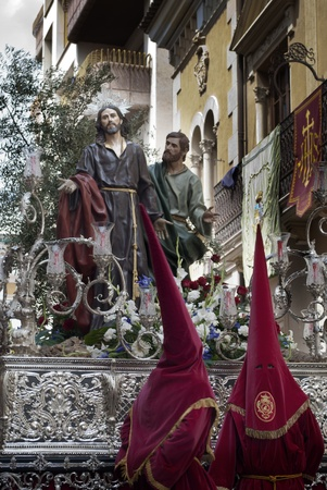 Couple of penitents with a Holy Week image during a procession in Jumilla  Spain  Stock Photo