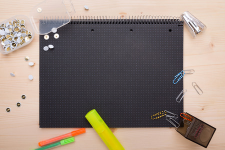 Different office objects arranged on a black piece of paper photo