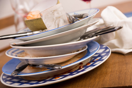 leavings: Set of dirty dishes on a wooden table
